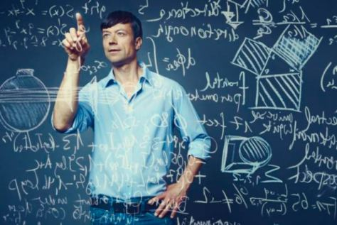 Happy mid-adult man standing in front of glass screen with mathematical formulas written on it