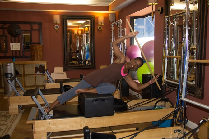 Owner Angelia Brown demonstrates spearing on a Reformer at Pilates of Jackson